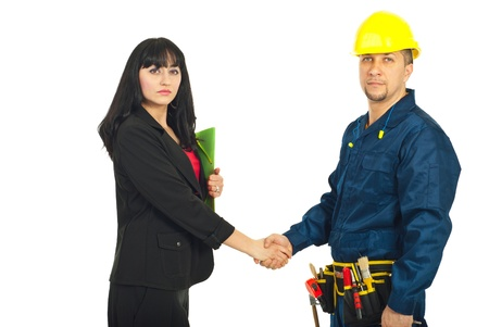 repairman: Business woman and constructor worker make a deal and shaking their hands isolated on white background