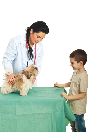 Happy kid coming with his puppy at veterinary woman for examination  photo