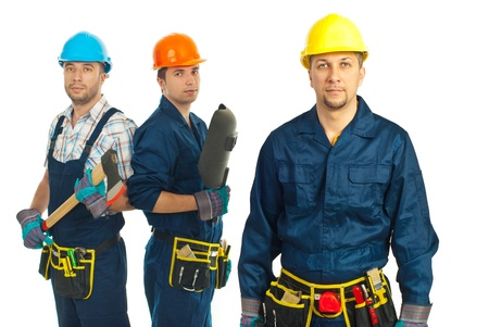Mid adult builder man standing in front of his team against white background photo
