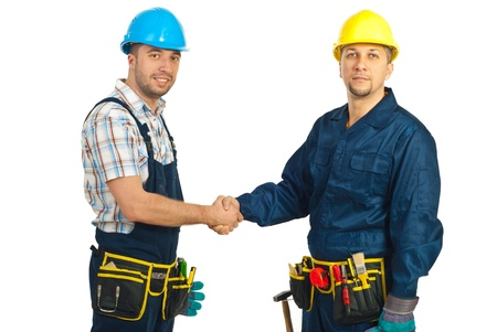 Two mid adults constructors workers giving hand shake isolated on white background photo