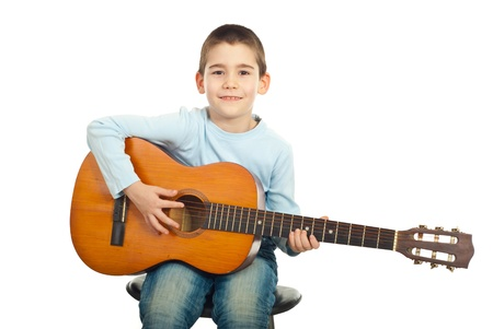 Small boy sitting on chair and playing acoustic guitar isolated on white background photo