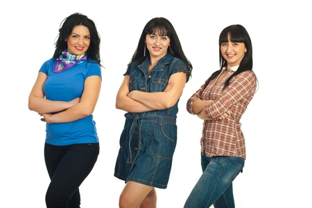 Row of three beautiful smiling women standing with arms folded in a row isolated on white background photo