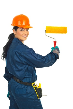 Happy painter woman holding paint roller isolated on white background photo