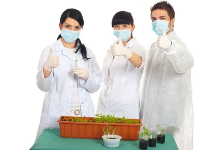 Successful scientists people in laboratory with new vegetables plants on their table giving thumbs up photo