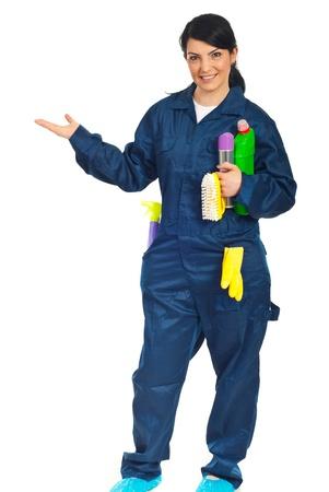schoonmaakartikelen: Reiniging werknemers vrouw holding reinigingsproducten en welkom met haar hand om te kopiëren ruimte geïsoleerd op witte achtergrond