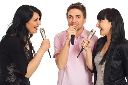 Happy three friends singing in microphones at karaoke party and having fun isolated on white background photo