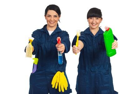 empleadas domesticas: Mujeres trabajadores feliz en uniforme que muestra productos de limpieza aisladas sobre fondo blanco Foto de archivo