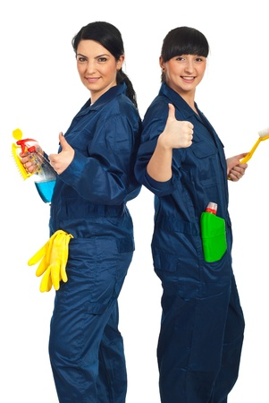 clean up: Successful team of cleaning workers women standing back to back holding products and giving thumbs up isolated on white background Stock Photo