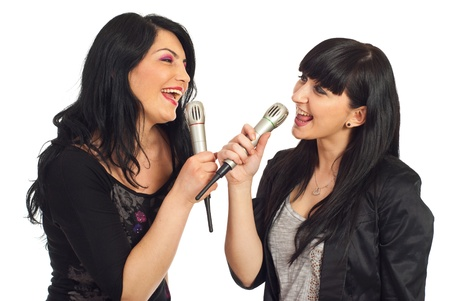 Two happy women singing to microphones and having fun isolated on white background
