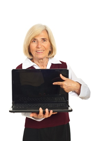 Senior smiling business woman pointing to blank laptop screen isolated on white background photo