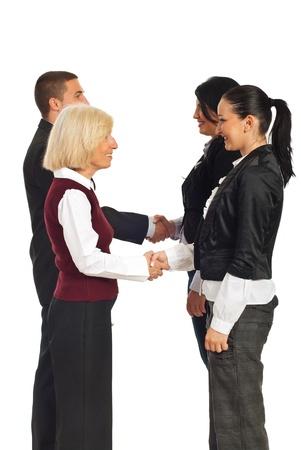 manos estrechadas: Cuatro empresarios dando handshakes y permanente una línea aisladas sobre fondo blanco