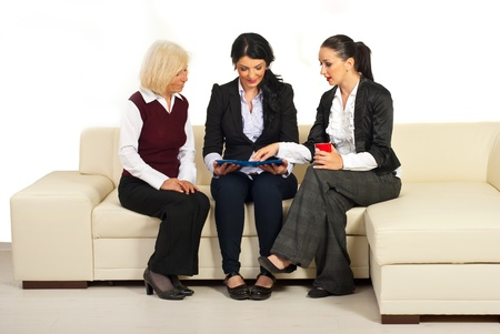 Three business people having conversation ,looking over folders  and sitting on a beige sofa in office photo