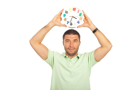Casual man in green t-shirt holding clock over his head isolated on white background photo