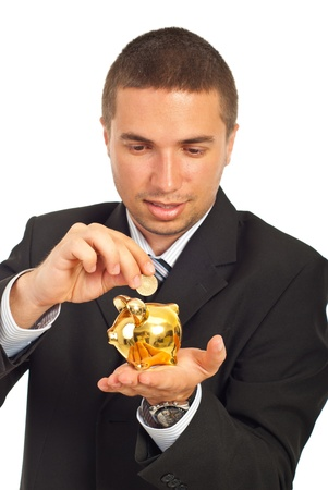 Happy business man putting coin in a gold piggy bank isolated on white background photo