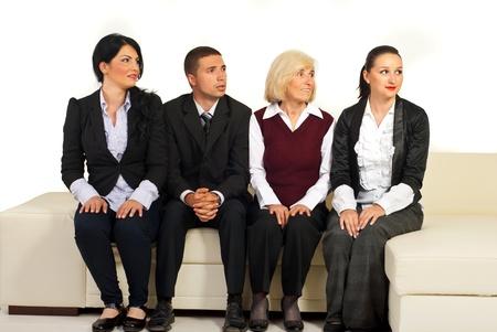 expresiones faciales: Cuatro empresarios sentado en una fila en el sof� y buscar en la parte derecha de la imagen con diferentes expresiones faciales en sus rostros