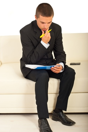 Thinking business man sitting on couch and holding papers photo
