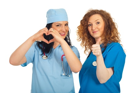 Two happy doctors women showing heart shape and giving thumb up isolated on white background Stock Photo - 9517230