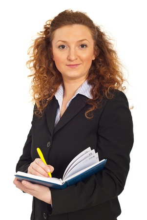 Redhead business woman writing in personal agenda isolated on white background photo
