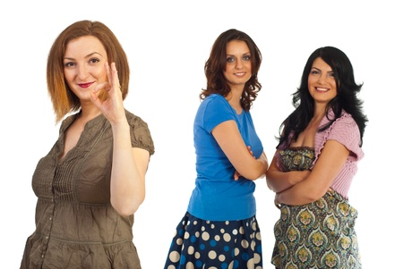Smiling woman showing okay sign hand gesture in front of her friends women isolated on white background photo