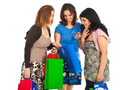 Three women friends looking and admiring  what they brought in a shopping bag isolated on white background Stock Photo - 9617500