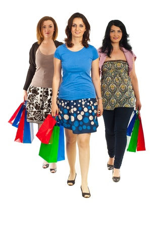 Full length of three women walking at shopping and holding colorful bags isolated on white background photo