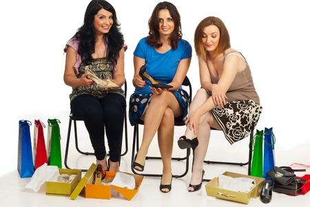 comprando zapatos: Felices tres mujeres tiendas de zapatos y sentados en sillas para  Foto de archivo