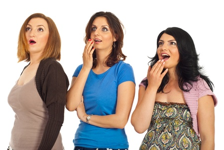 awe: Surprised three women standing in a line and looking up isolated on white background Stock Photo