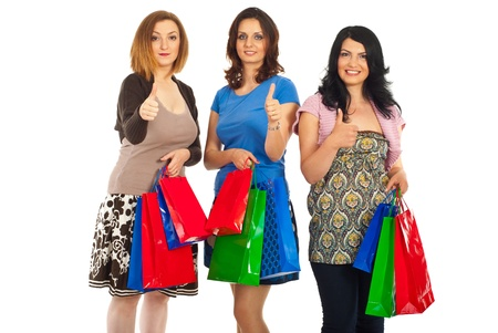 Three women standing in a row giving thumbs up and holiding colorful shopping bags isolated on white background photo