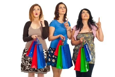 Three amazed shoppers women with shopping bags looking and pointing up isolated on hwite background Stock Photo - 9617548
