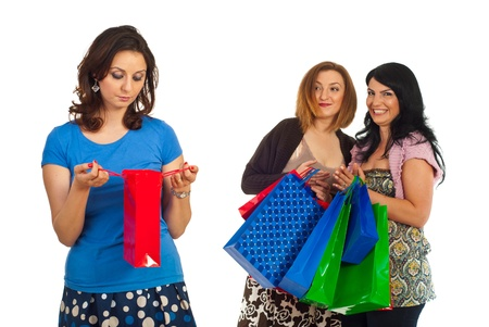 selfish: Sad woman of small shopping bag and two selfish women woith many bags laughing and joking about their friend isolated on white background Stock Photo