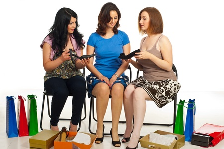 Three woman in a shop choosing shoes,compare different shoes and having conversation photo