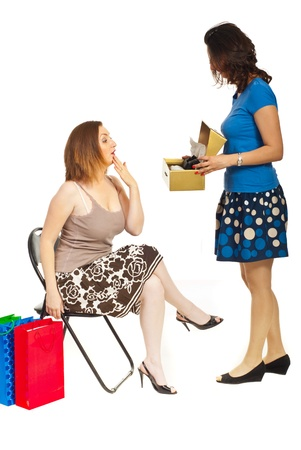 Clerk showing new shoes to a customer woman with surprised face  over white background photo