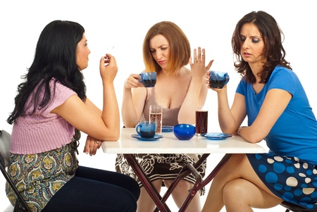 Three women sitting on chairs at table and two of them drinking bad coffees Stock Photo