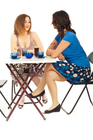 sitting at table: Two women having happy conversation and sitting at table in a cafe shop isolate don white background