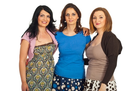 Happy three women friends embracing together and smile isolated on white background photo