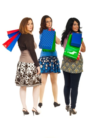 Three women walking holding shopping bags on their shoulders and looking back isolated on white background photo