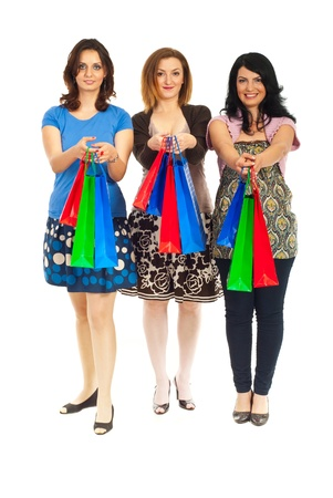 Full length of happy three women in a row giving colorful shopping bags isolated on white background Stock Photo - 9617575