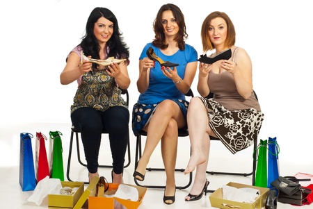 Happy women friends sitting on chairs in a shop place and showing their new shoes Stock Photo - 9617583