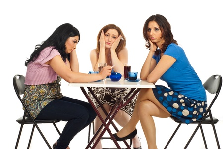 Unhappy three women sitting on chairs at table in a cafe shop and being upset each other  or  received bad news  photo