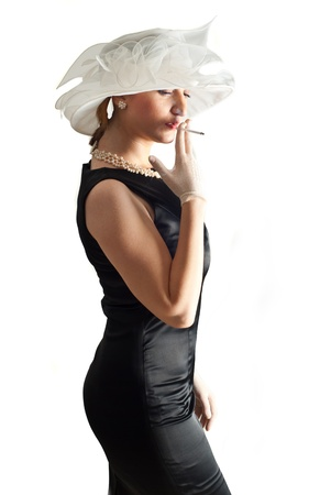semi dress: Elegant woman in black satin dress and  white veil hat smoking and standing in semi profile