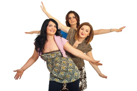 woman in white: Smiling group of women friends standing with arms up isolate don white background Stock Photo