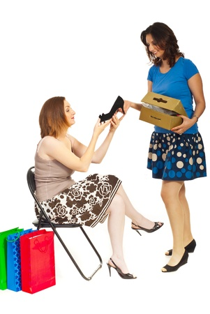 Smiling clerk showing new shoes to a customer woman in a shop place over white background photo