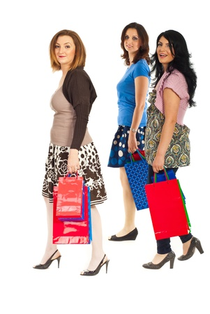 Full length of cheerful shoppers women with bags walking to shopping isolated on white background
