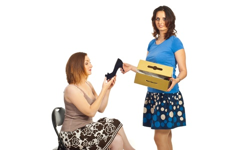 Seller smiling woman showing new shoe to a client woman on chair over white photo