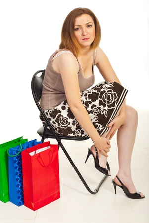 Tured woman of shopping sitting on chair and touching her hurting legs  photo