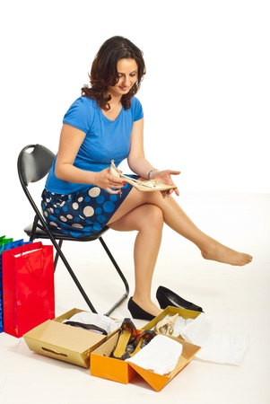 shoe box: Woman sitting on chair in a shopplace and admiring new shoes against white background