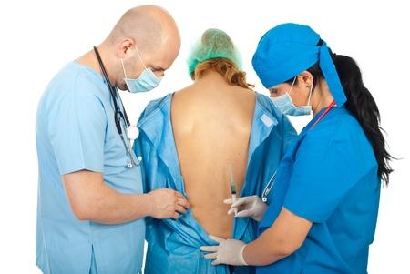 Two surgeons preparing to make epidural anesthesia to pregnant woman isolated on white background photo