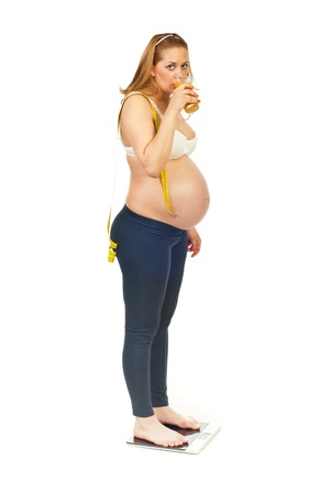 Pregnant woman standing in profile on a scale holding centimeter on shoulder and drinking fresh of orange juice isolated on white background photo