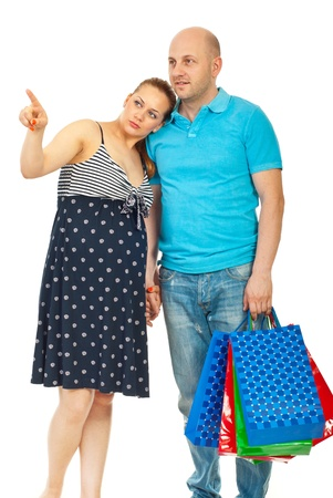 Pregnant woman pointing and showing something to her husband at shopping isolated on white background photo
