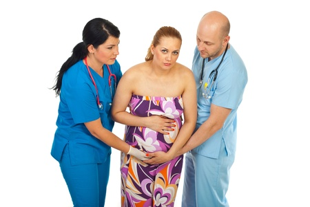 contractions: Two doctors helping pregnant woman with painful tummy isolated on white background